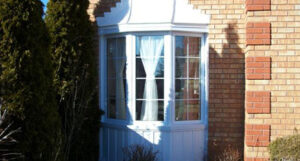 A new white bow window in a brick house - Linton Window & Door