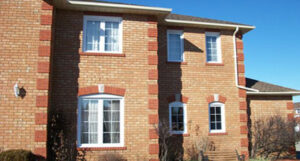 A brick house with new sliding windows installed - Linton Window & Door